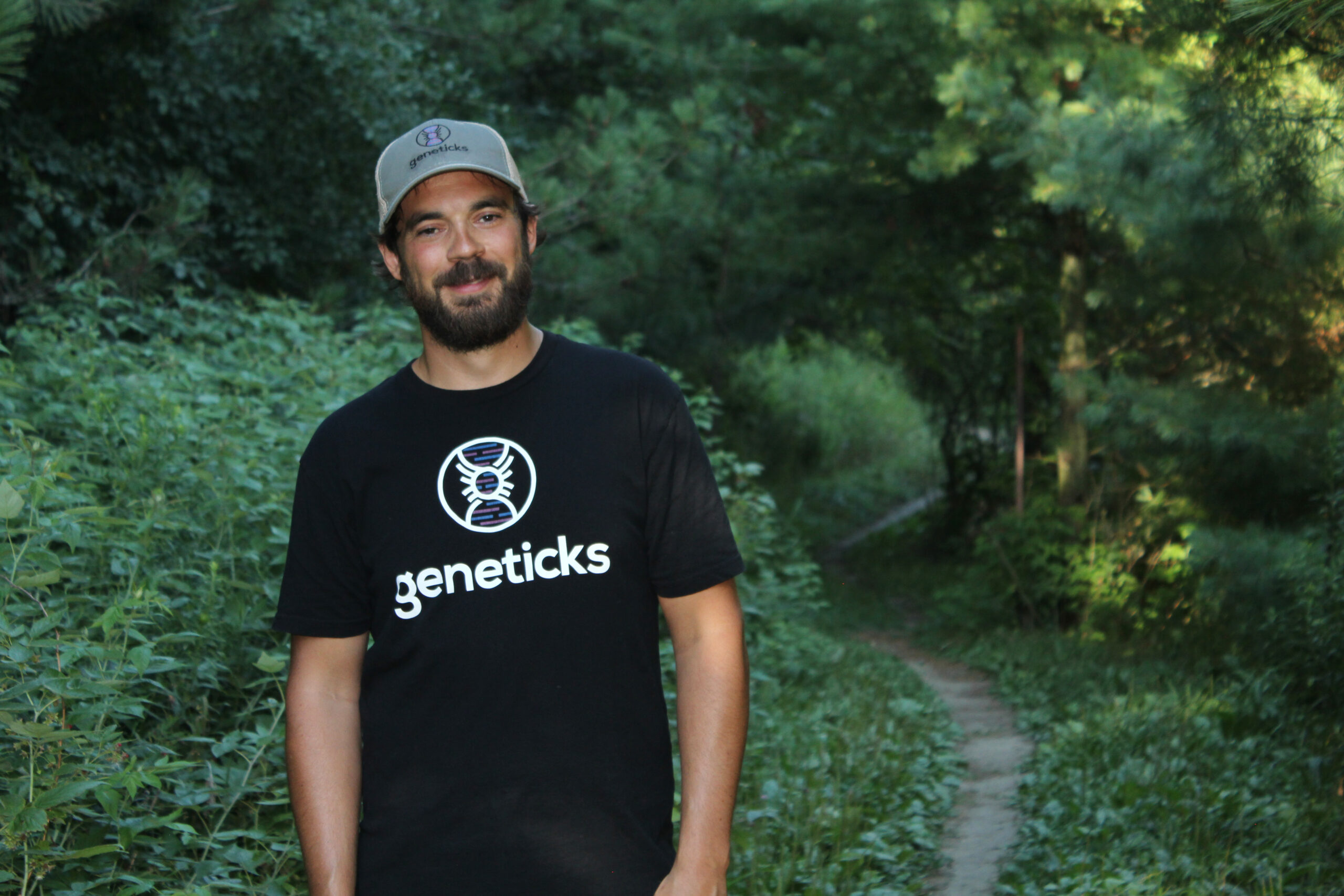 A young white male in a black T shirt that reads geneticks and a greenbaseball hat stands in front of woods